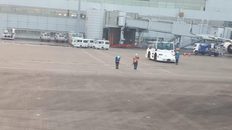 飛行機を見送るセンダー作業員の写真